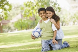 Two children playing football in park